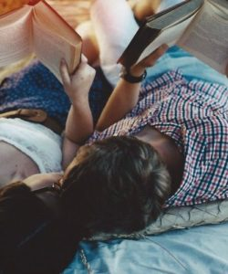Couple kissing while reading a book